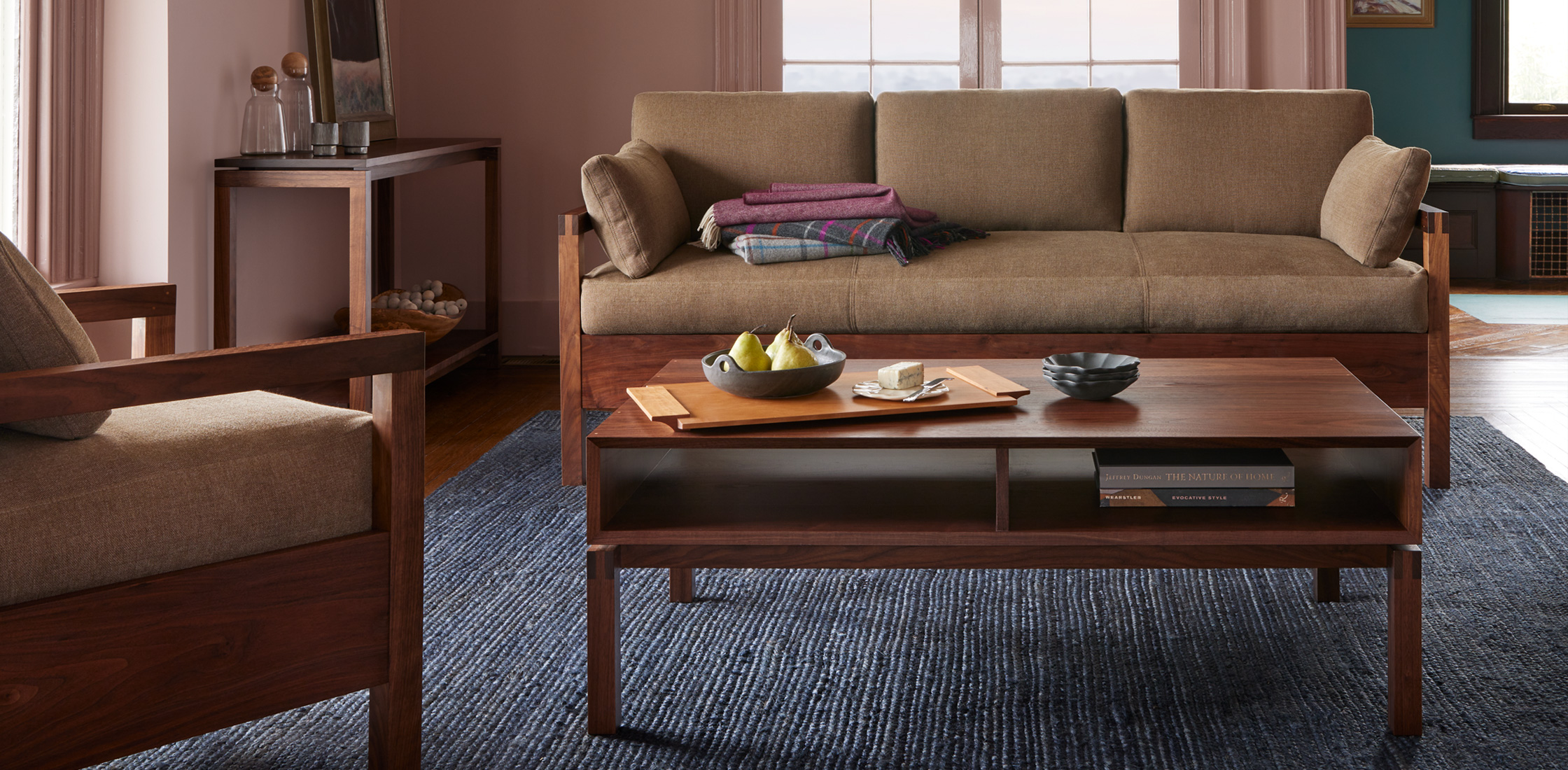 Living room featuring a studio chair, sofa, coffee table and serving tray. | View Holiday Sale